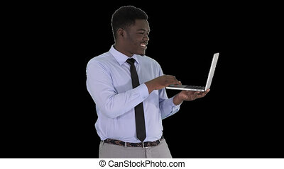 Talking to camera young african man with laptop in his...