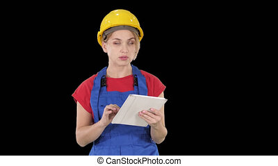 Woman engineer checking building plan on touchpad and looking at objects, buildings around her, Alpha Channel