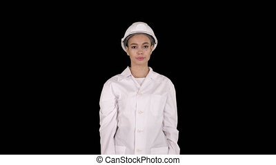 Woman engineer in white robe and white hard hat walking, ...