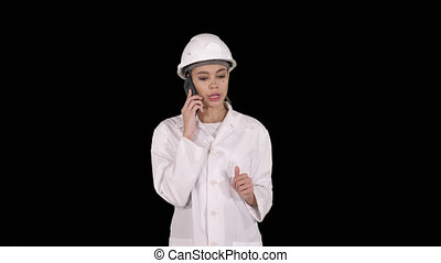 Woman engineer talking on the phone while walking, Alpha Channel