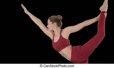 Yoga teacher practising pose dandayamana dhanurasana, Alpha...