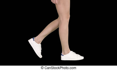 Women feet wearing white sneaker shoes walking, Alpha...
