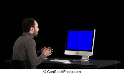 Young business man making video call on his computer, Alpha Channel. Blue Screen Mock-up Display.