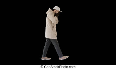Caucasian man in a hat and coat coughing walking, Alpha Channel