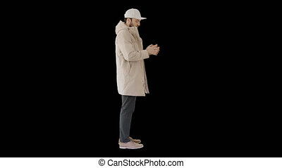 On Alpha Matte. Wide shot. Side view. Man in winter clothes using sanitizer spray to prevent flu disease, Alpha Channel. Professional shot in 4K resolution. 53. You can use it e.g. in your medical, commercial video, business, presentation, broadcast