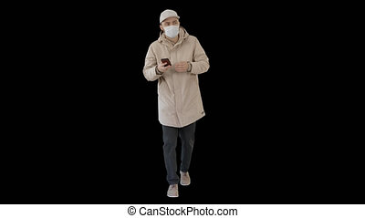 On Alpha Matte. Wide shot. Young casual man walking making a call wearing warm clothes and protective mask, Alpha Channel. Professional shot in 4K resolution. 53. You can use it e.g. in your medical, commercial video, business, presentation, broadcast