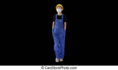 On Alpha Matte. Wide shot. Young woman in yellow hardhat and in medical mask walking, Alpha Channel. Professional shot in 4K resolution. 53. You can use it e.g. in your medical, commercial video, business, presentation, broadcast