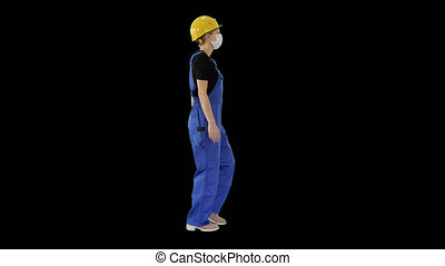 Young woman in hard hat and medical mask walking, Alpha ...