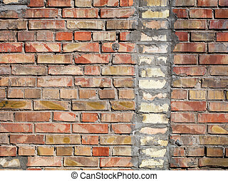 On an old wall of red bricks a separated vertical fragment of the old silicate brick