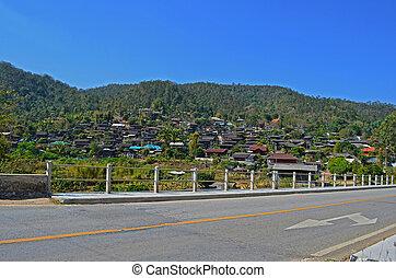 On Asphalt Road pass Country Village 1_2, Bridge, Blue Sky, Direction, Traffic Sign, Maehongson province, Thailand