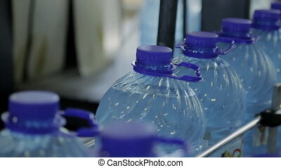 On assembly line going full plastic water bottle with transparent lid.