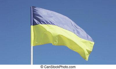 On background of blue sky Ukrainian flag