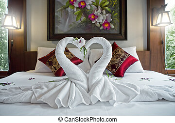 close up view of two nice towels swans on white bed sheet