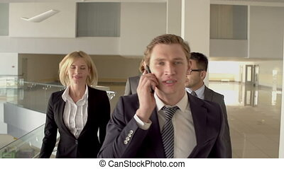 Business team walking towards camera, everybody following guy talking on the phone in slow motion