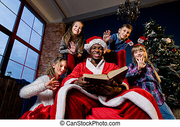 On Christmas Eve, Santa Claus reads the Christmas story for children who listen to him from all sides, on the background of a Christmas tree.