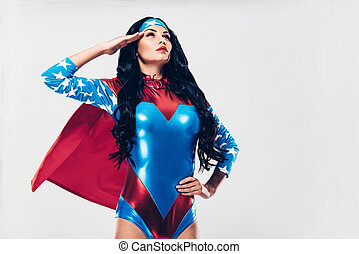 On duty with fighting crime. Low angle view of beautiful young woman in superhero costume looking away and holding hand near head while standing against white background