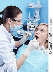 On examination in dentistry - The dentist examines a patient