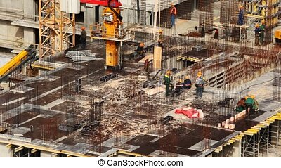 On floor of under construction building workers are engaged in building