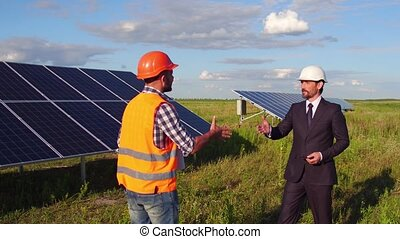 On footage director metting foreman in the field at solar energy station.