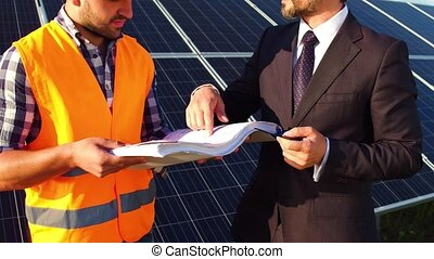 On footage engineer and businessman discussing technical drawings, solar panels behind them.