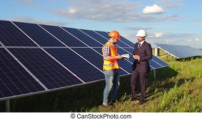 On footage foreman and business client meeting in the field at solar energy station.