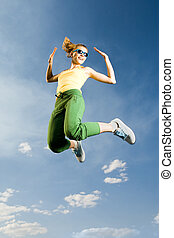 On height - Image of cheerful girl in high jump against...