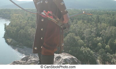 On high rock stands an archer in an old uniform with a bow....