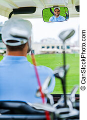 On his way to the next hole. Young happy male golfer driving a golf cart and looking at rear view mirror