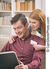 On-line shopping with credit card - Happy couple doing...