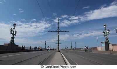 On Liteyny bridge with tram tracks are walking pedestrians