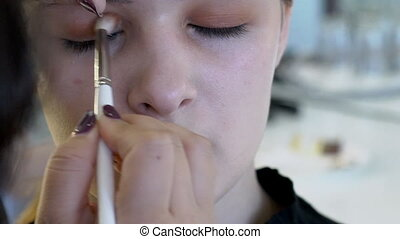 On model face make-up artist applies orange shadows to eyelids.