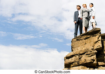 Photo of three business partners standing on the mountain top with cloudy sky above them