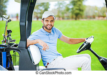 On my way to the next hole. Side view of young happy male golfer driving a golf cart and looking at camera