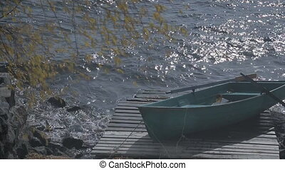 On pier there is wooden boat against background of strong waves in fall.