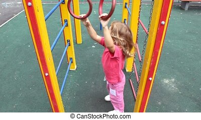 on playground on game equipment girl on ladder shakes