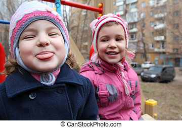 On playground the girl puts out  tongue,  second laughs