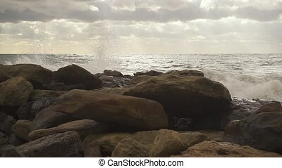 On rocks on the shore a wave breaks slow mo