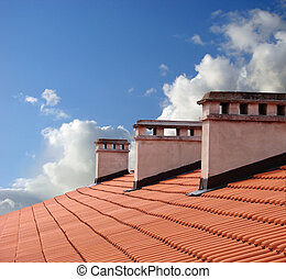 On roof - Chimneys on roof of red tiles with blue sky and ...