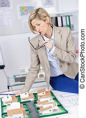 on scale model of house and architect woman