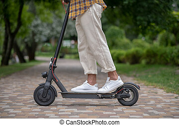Man standing on a scooter in the park