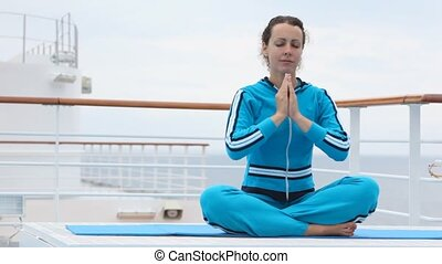 on ship deck woman on rug sits in lotus pose prayerfully...