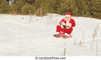 On sled - Santa sliding down the hill and waving cheerfully