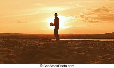 on sunset background silhouette of a man pumping up the ball slow motion video