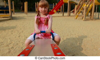 Little girl on swings looking at camera