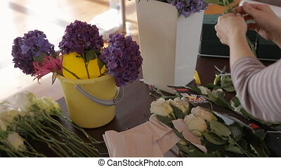On table among lush flowers florist breaks petals of white...