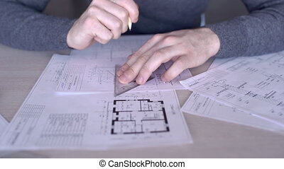 On table architect's hands make a drawing with a pencil and ruler.