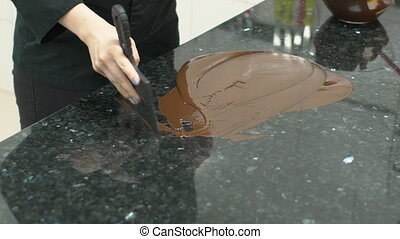 On table confectioner conducts tempering the chocolate with...