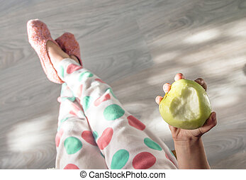 on the background of a beautiful wooden floor baby legs in pajamas in polka dots and knitted slippers pastel tones hand holding an apple bite in the shape of a heart