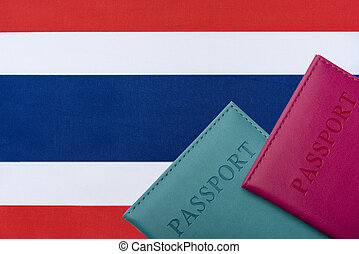 On the background of the Flag of Thailand lie a passport.