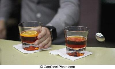 bartender prepare cocktail with orange